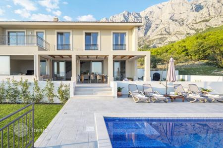 Coastal houses for sale in Makarska. Two-storey villa with swimming pool, plot of land and sea view in Croatia, Makarska Riviera