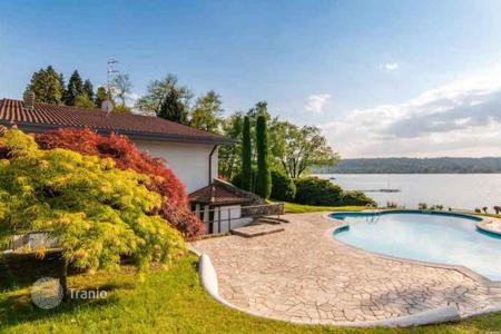 Luxury houses with pools for sale in Maggiore (Italy). Spacious villa with swimming pool, tennis court and guest house on the shore of Lago Maggiore, with direct access to the dock bay!