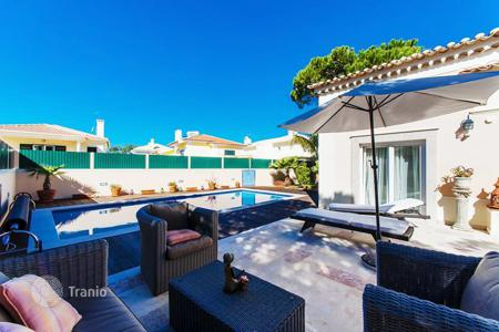 Luxury houses for sale in Cascais. Family two-storey house with a terrace and a swimming pool under the open sky in Cascais