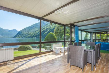 Houses with pools for sale in Lombardy. Two-level villa with a garden, a swimming pool, a sauna and a view of the lake Lugano and the mountains, Osteno, Italy. Permit for moorage