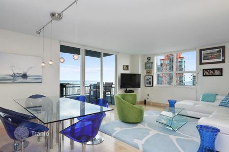 Apartments with pools for sale in North America. Two-bedroom apartment with spacious terraces and ocean views, in a modern condominium with a swimming pool, Miami Beach, Florida, USA