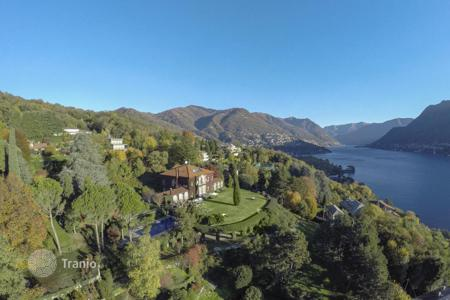 Luxury houses with pools for sale in Lake Como. Manor consists of 3 buildings, park and garden on lake in town Como
