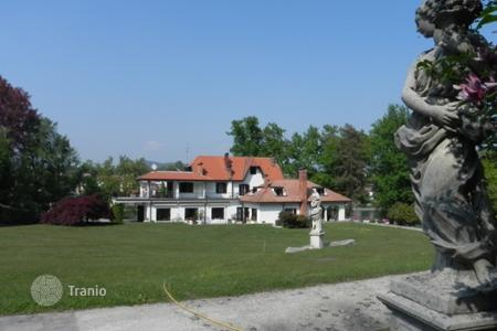 Houses with pools for sale in Castelletto sopra Ticino. Villa of large size, lakefront with dock surrounded by lush park