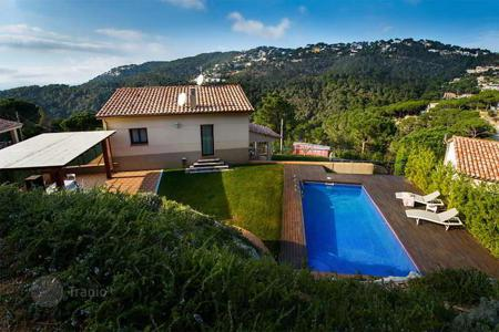 Houses with pools for sale in Catalonia. Two-storey villa with a fireplace, a swimming pool, a garden, and a terrace, in a green district of Lloret de Mar, Spain