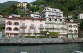 Apartments with pools for sale in Lake Como. Spacious apartment with a lake view and a parking in a residence with a garden and a swimming pool, Menaggio, Italy