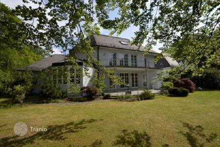 Houses for sale in Bavaria. Snow-white house with a garden and a large plot near the river Isar in Grünwald, Munich