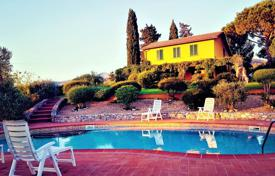 Houses with pools for sale in Italy. Luxury villa immersed in a large park with typical Mediterranean vegetation plants and olive trees in Tuscany, Italy