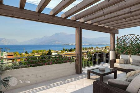 Apartments with pools for sale in Garda. Penthouse with lake view, private garage and a parking place, Desenzano del Garda