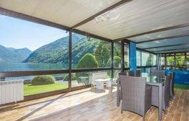 Luxury 5 bedroom houses for sale in Lombardy. Two-level villa with a garden, a swimming pool, a sauna and a view of the lake Lugano and the mountains, Osteno, Italy. Permit for moorage.