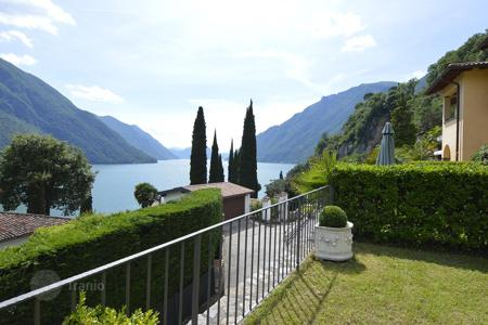 Townhouses for sale in Italian Lakes. Townhouse with terrace, private garden and stunning views of the mountains, forest and the lake of Lugano, Lombardy, Italy