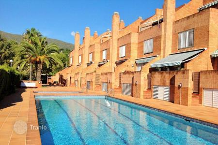 Property for sale in Castelldefels. Sea and mountain view townhouse with 2 terraces, in a residence with pool and parking, on the first line of the sea, in Castelldefels, Spain
