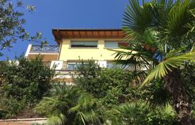 Luxury houses for sale in Lake Garda. Modern villa of two furnished apartments with a garden, an outdoor pool and panoramic views of Lake Garda, Padenghe sul Garda, Italy