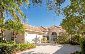 Houses with pools for sale in North America. Spacious cottage with a garage and a terrace on the bank of the canal in West Palm Beach, Florida, USA