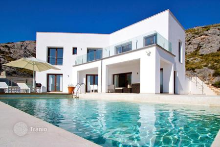 Luxury houses with pools for sale in Majorca (Mallorca). Snow-white villa on a hill, Pollensa, Spain. Furnished house with a terrace with a barbecue area and an infinity-pool, near the town center